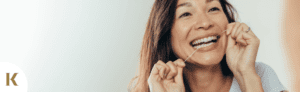 woman taking care of her teeth by flossing